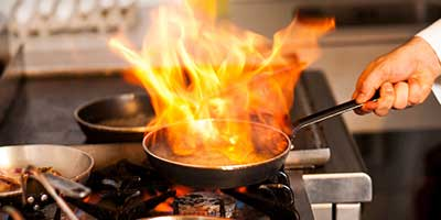 Hot fire in pan on professional gas range